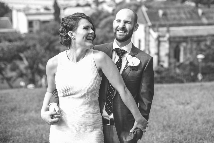 Braut und Braeutigam im Park mit Stadt-Kulisse