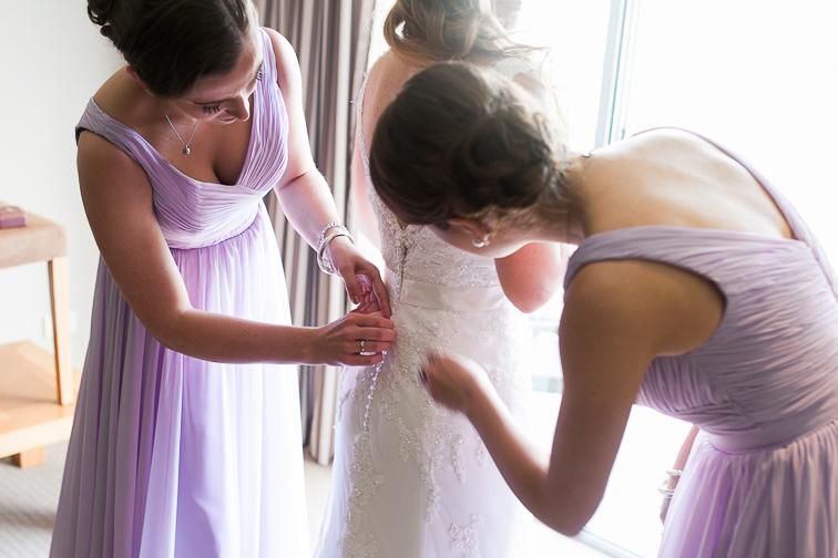 Kleid von der Braut wird von Trauzeugen zu geknoepft