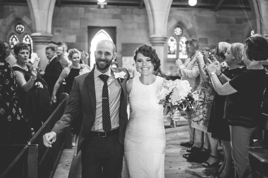 Ehepaar verlaesst glücklich die Kirche