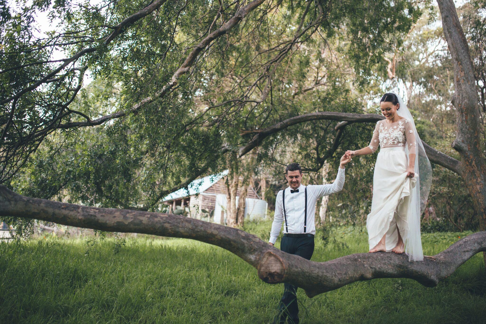 Braut balanciert mit Hilfe des Braeutigams auf einem Ast