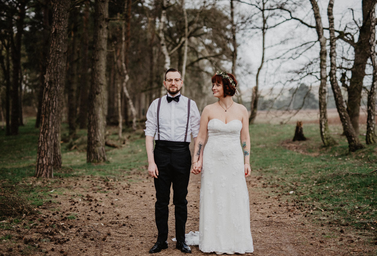 Brautpaar steht im Wald nebeneinander und ist sehr glücklich
