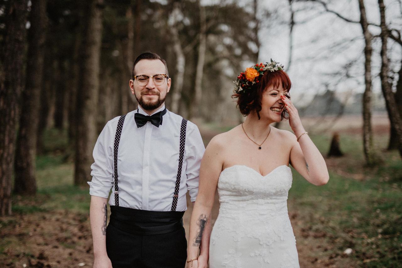 Brautpaar lacht im Wald und Braut hält sichd ie Hand vor Ihr Gesicht