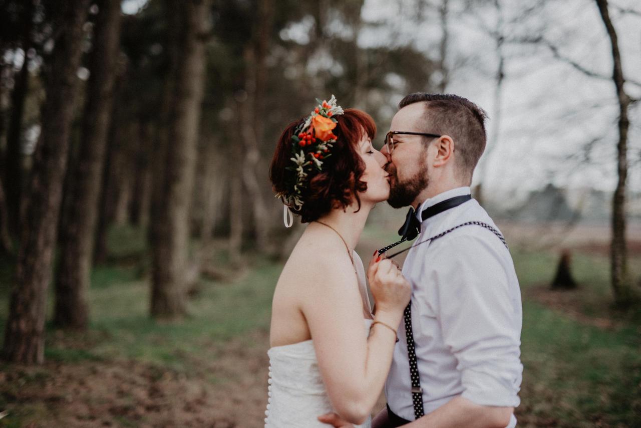 Brautpaar küssr sich und Braut hält sich an Hosenträgern des Bräutigams fest