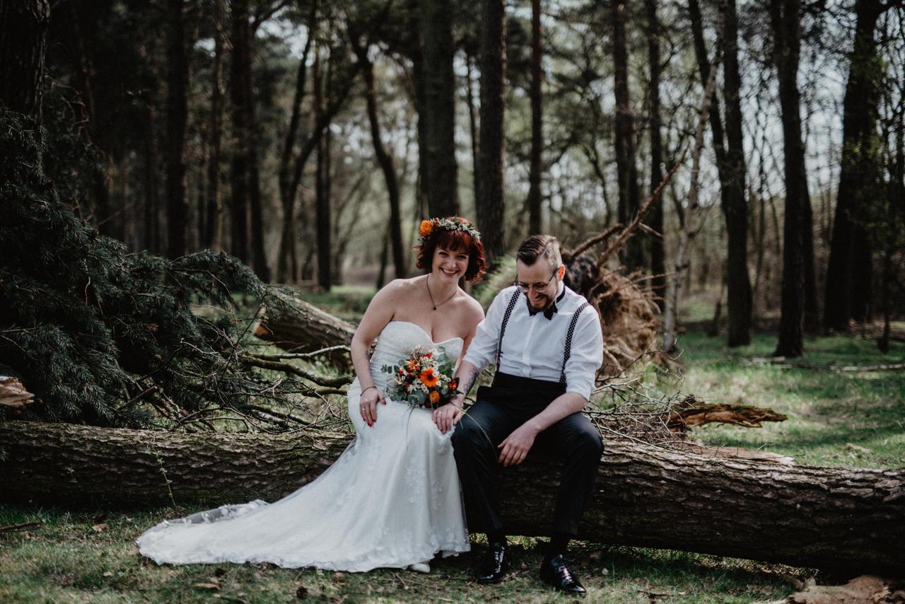 Brautpaar sitzt auf Baumstamm im Wald