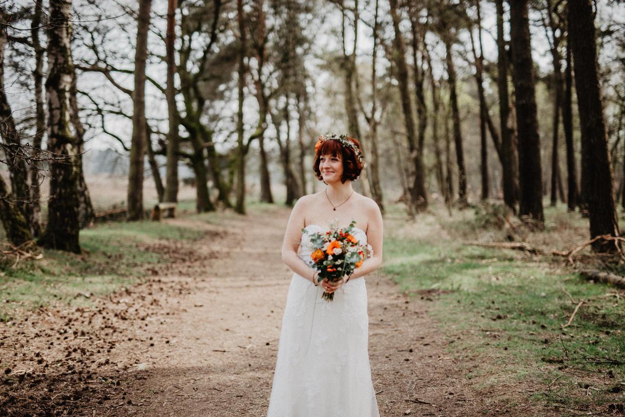 Braut steht im Wald mit Brautstrauß