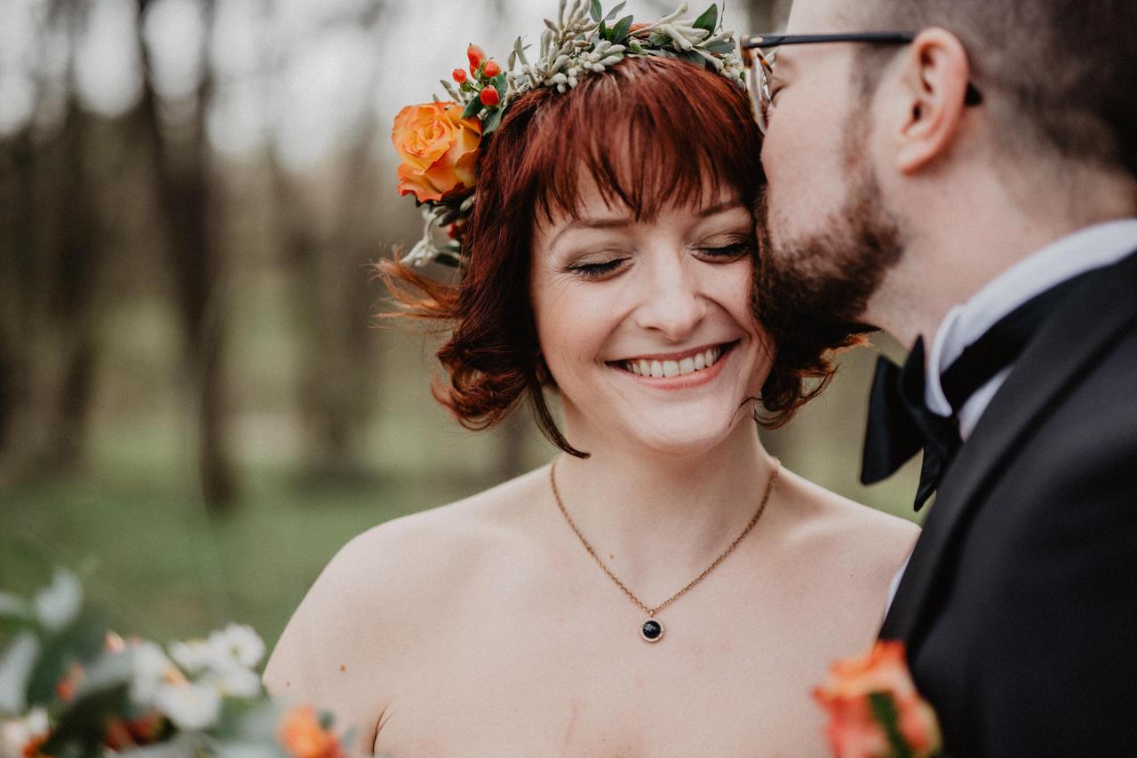 Bräutigam küsst Braut im Wald auf den Kopf