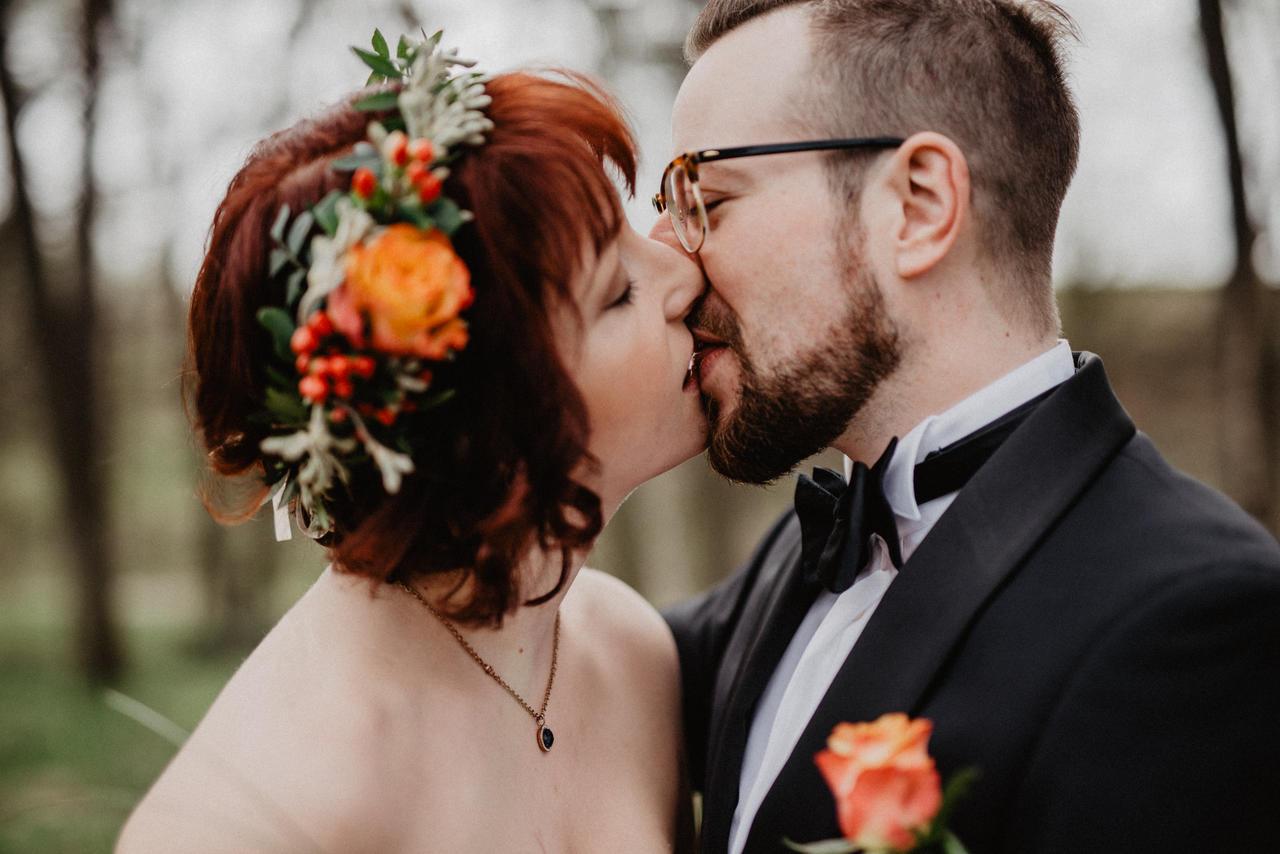 Brautpaar küsst sich im Wald auf den Mund
