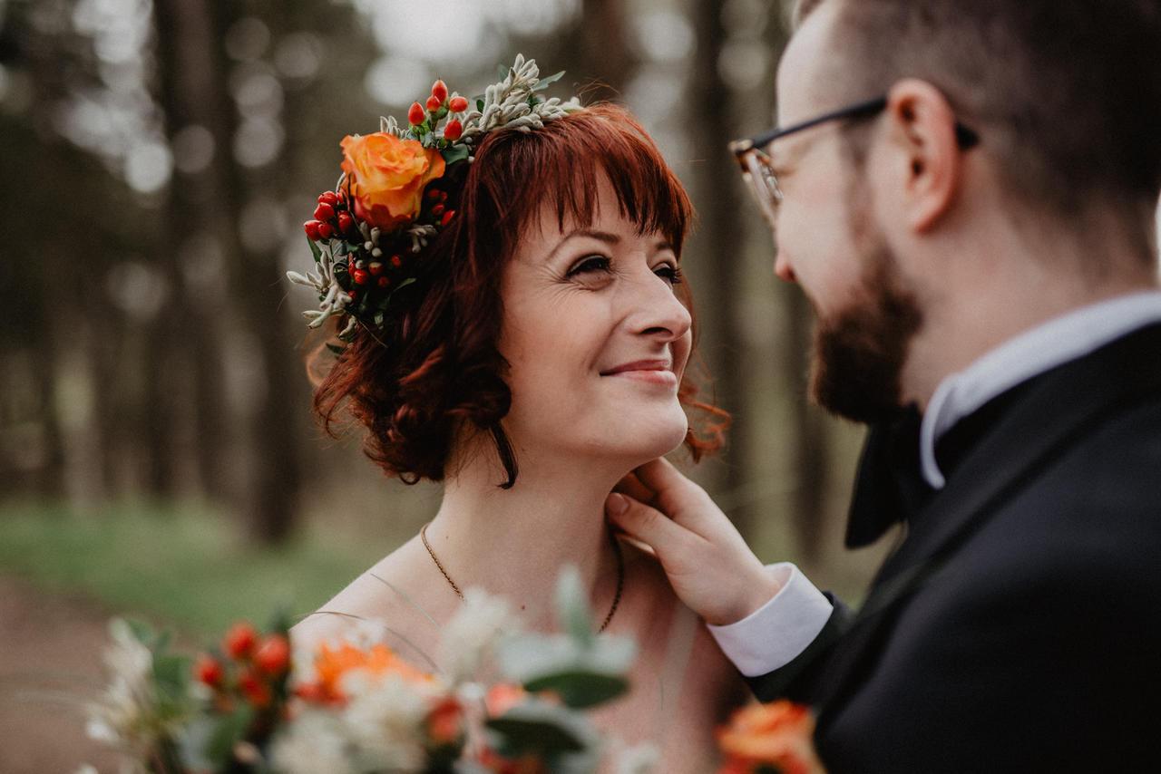 Brautpaar guckt sich tief in die Augen im Wald