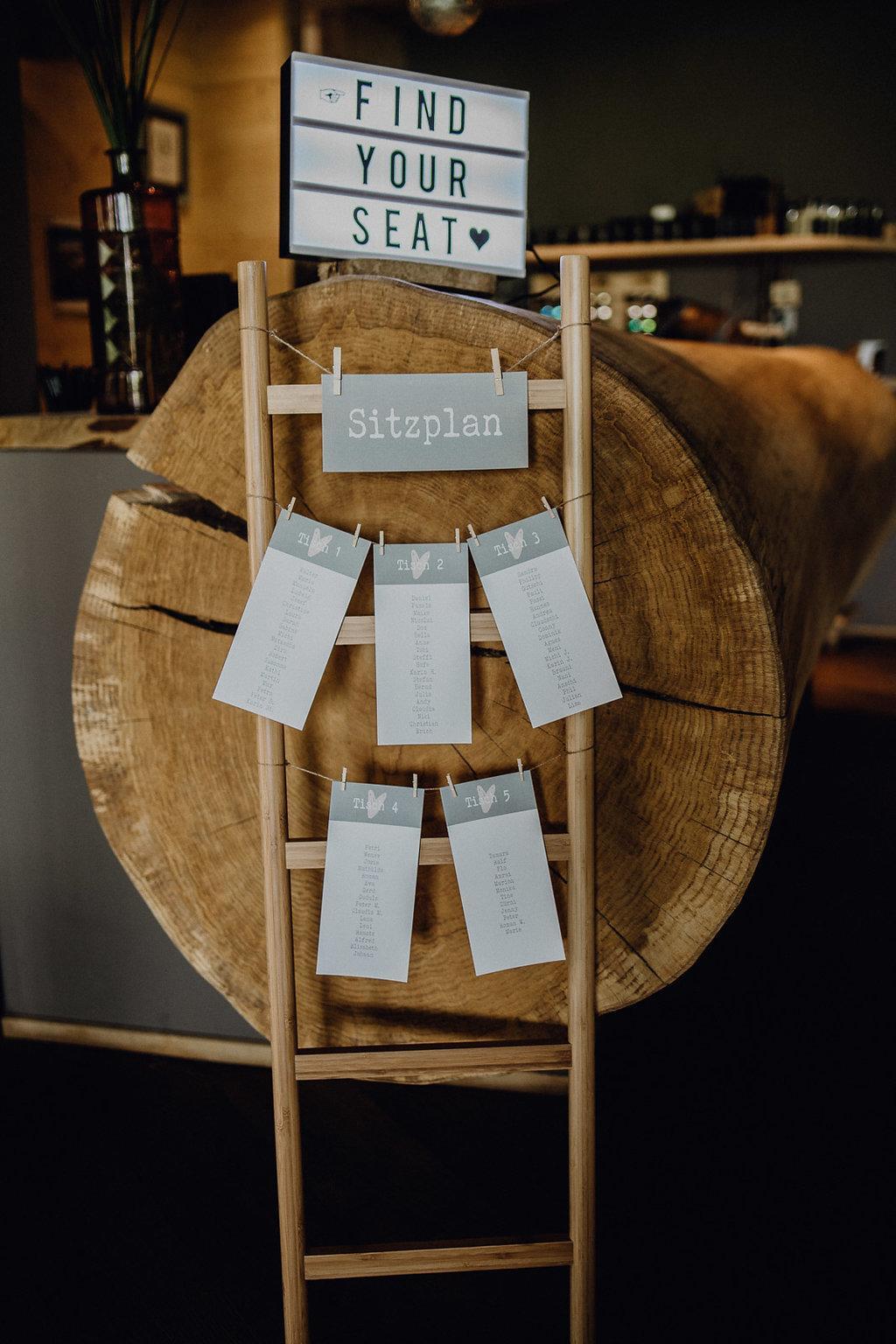Sitzplan in grau an einer braunen Holzleiter