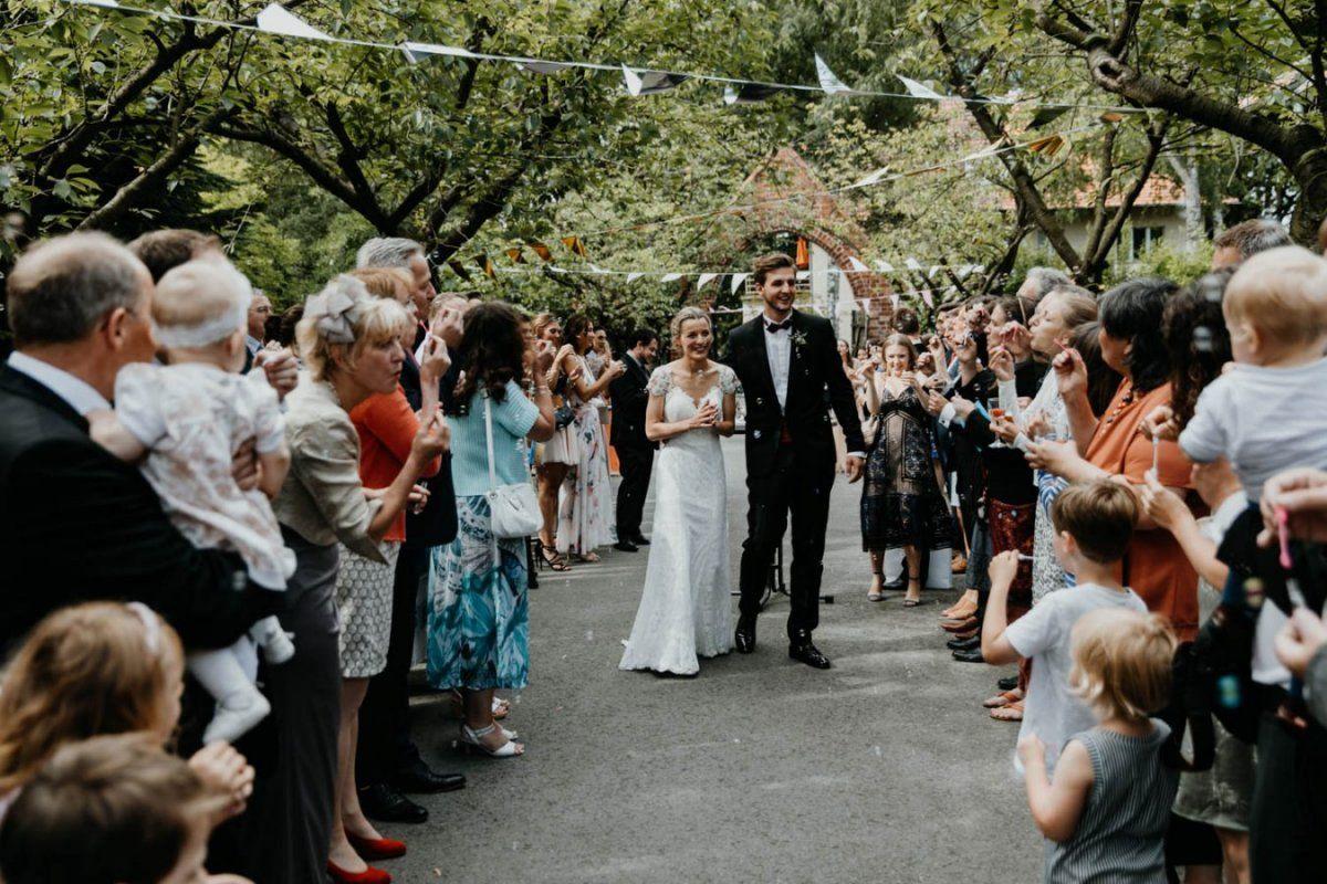 Hochzeitsgäste pusten Seifenblasen auf das Brautpaar
