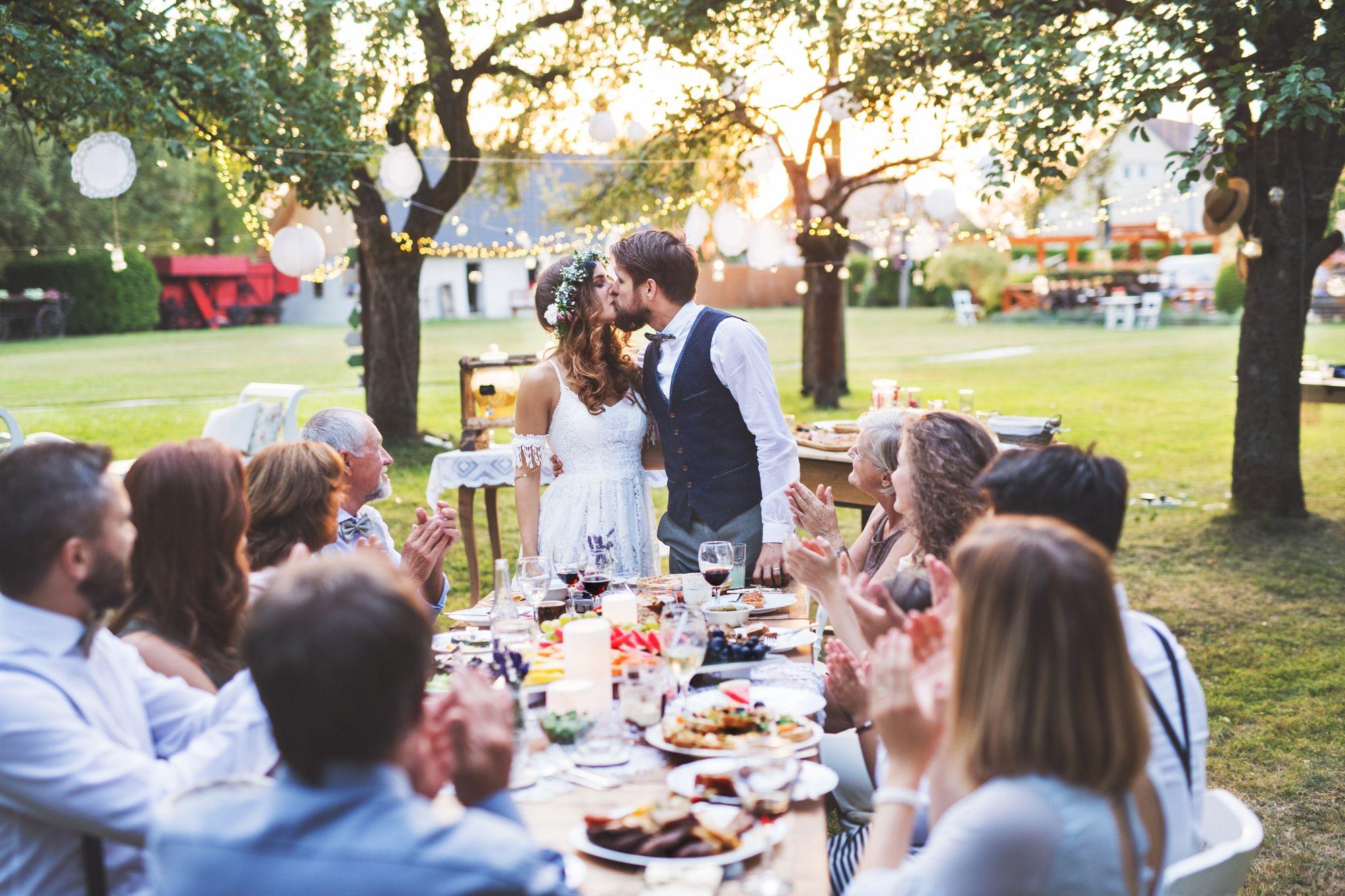 Hochzeitspaar küsst sich auf der Gartenhochzeit vor den Gästen