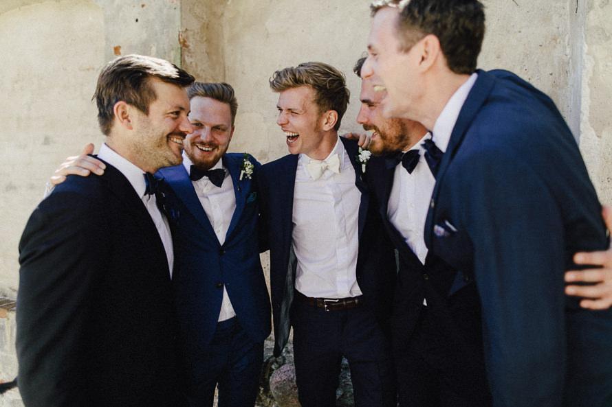 Bräutigam lacht zusammen mit seinen Trauzeugen
