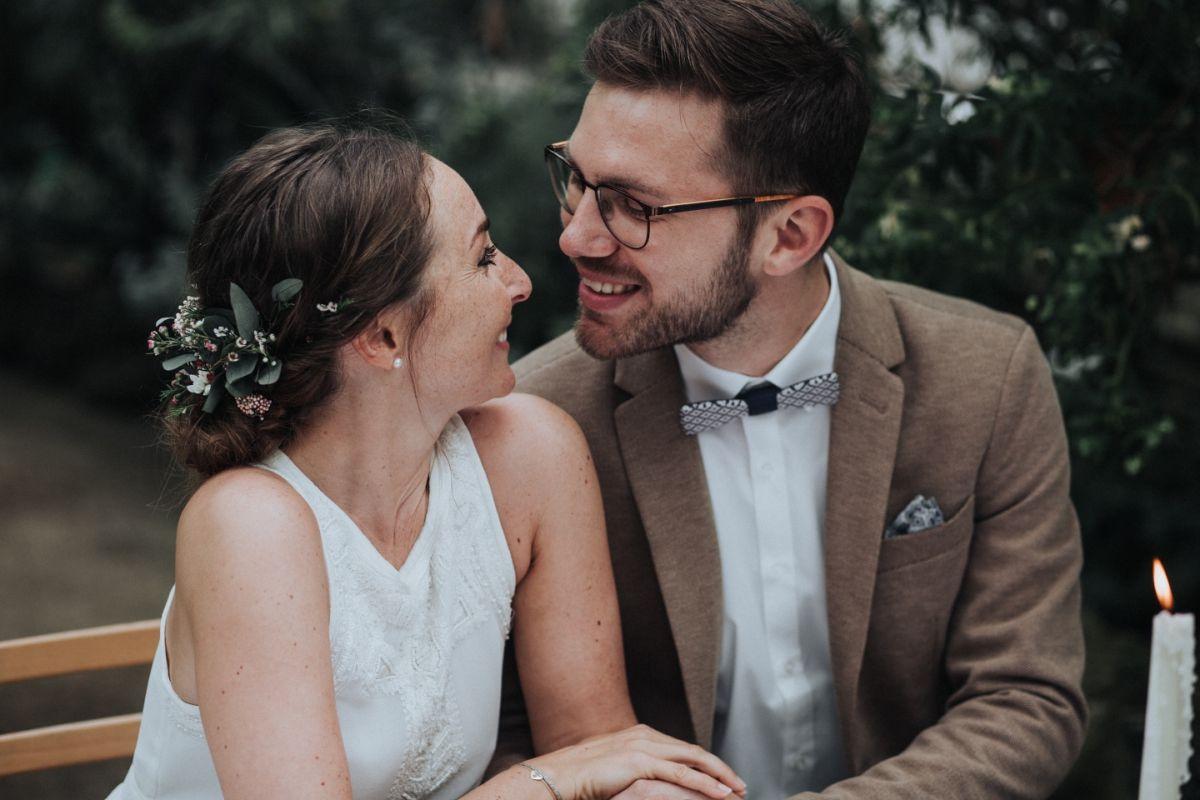 Braut mit floralem Haarschmuck und Bräutigam mit Holzfliege