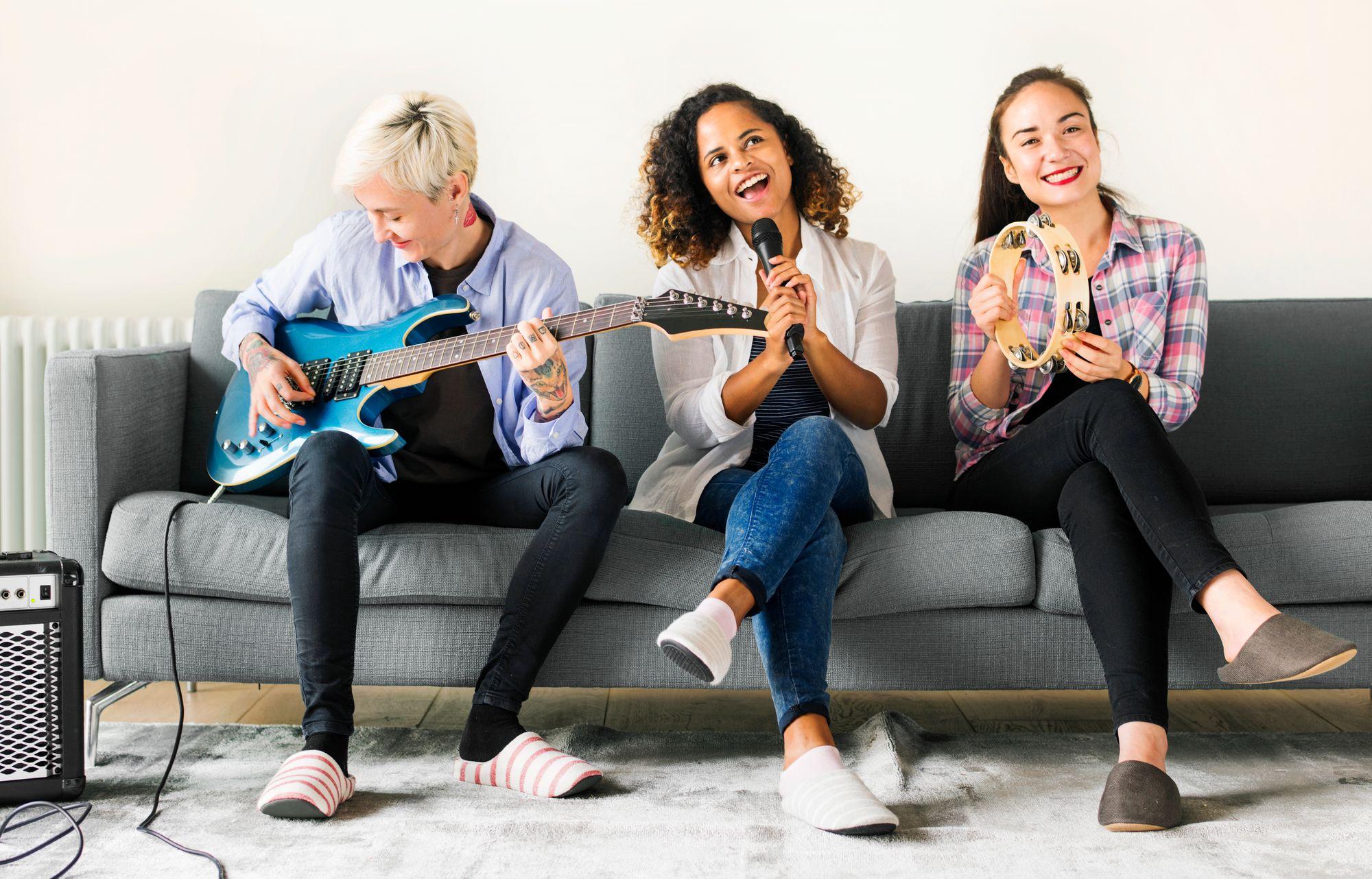 Karaoke auf dem Junggesellinnenabschied, drei Frauen singen auf einer Couch