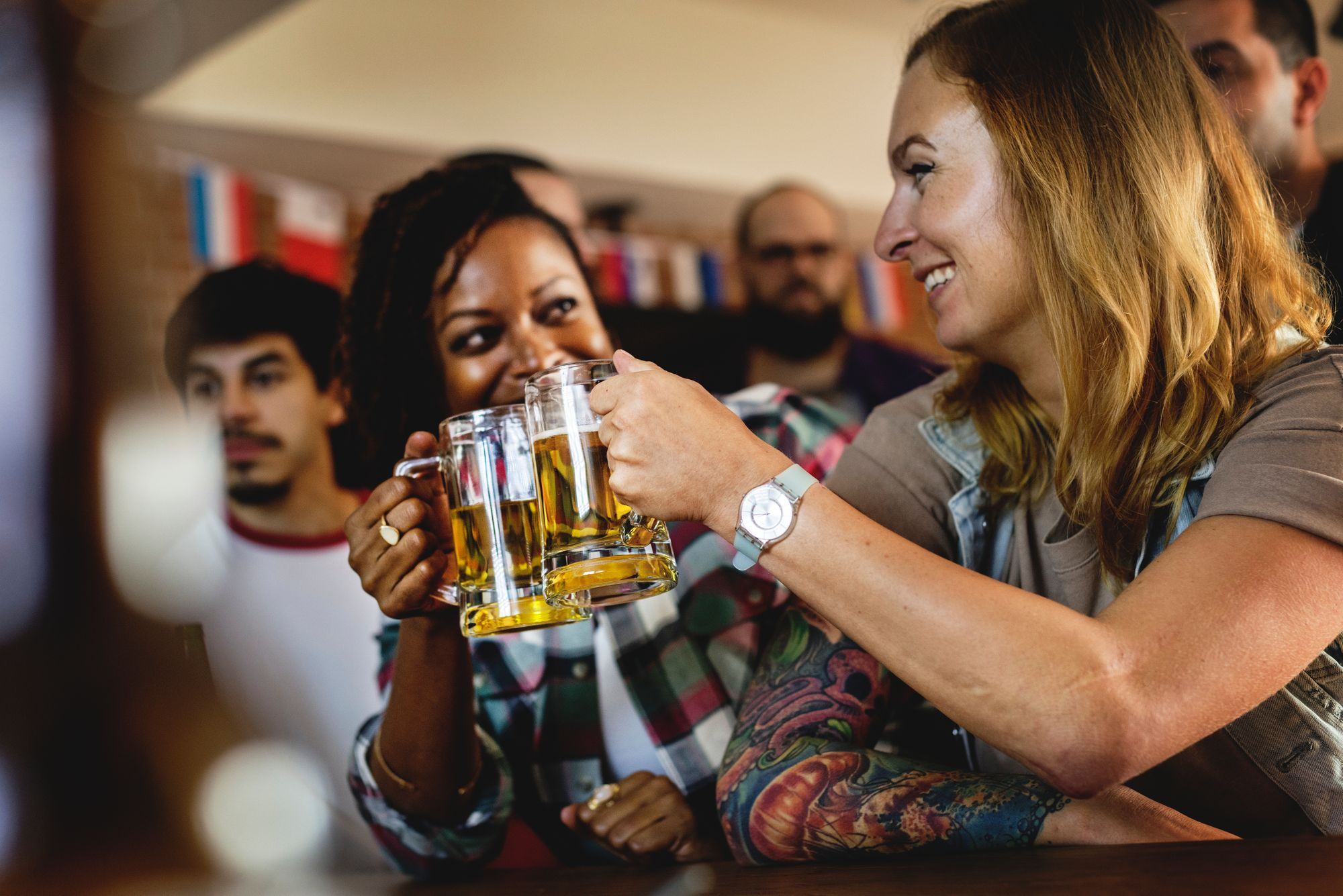 zwei Frauen stoßen beim Junggesellinnenabschied mit Bier an
