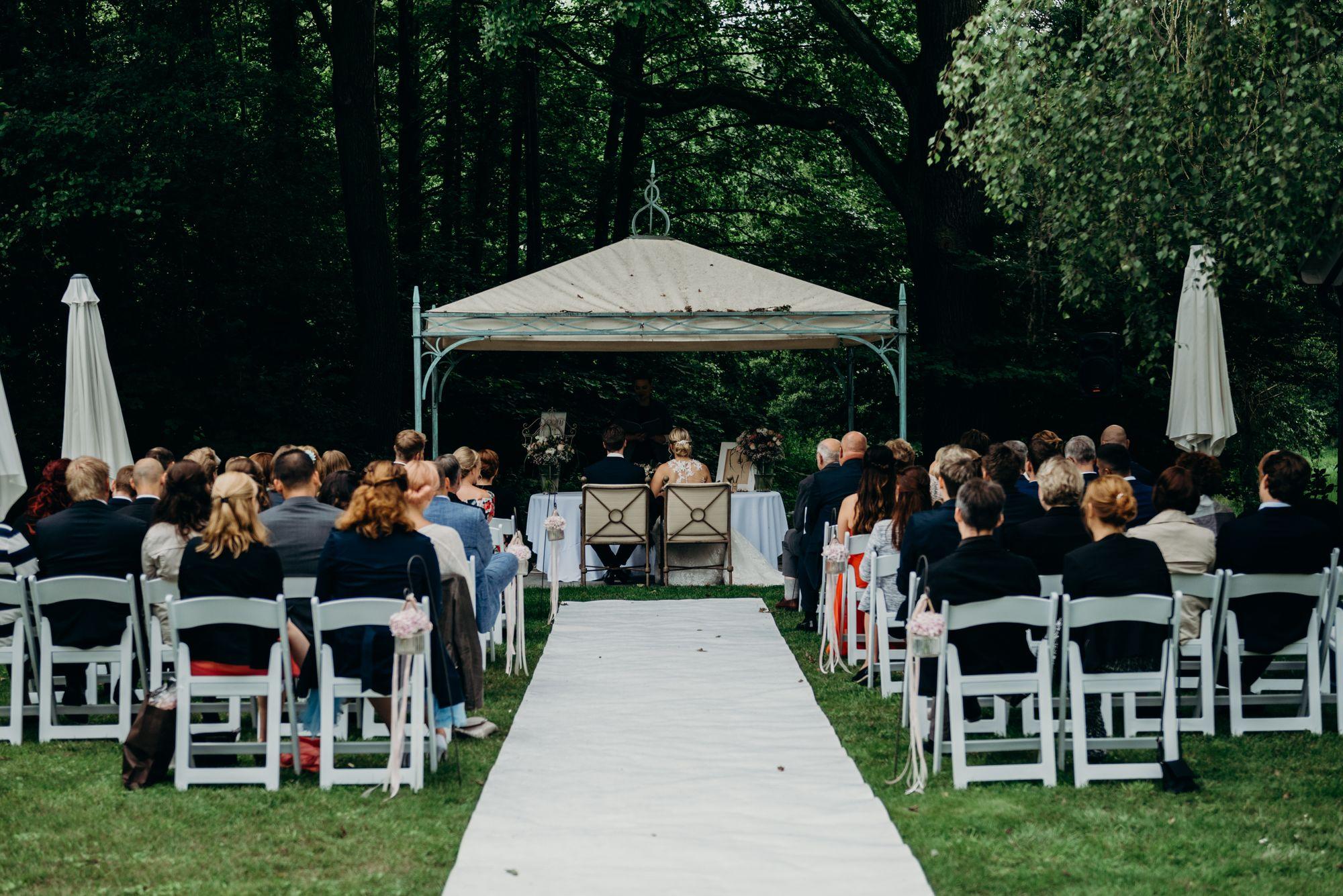 Trauung im Garten unter einem Pavillion mit dem Brautpaar und dem Trauredner