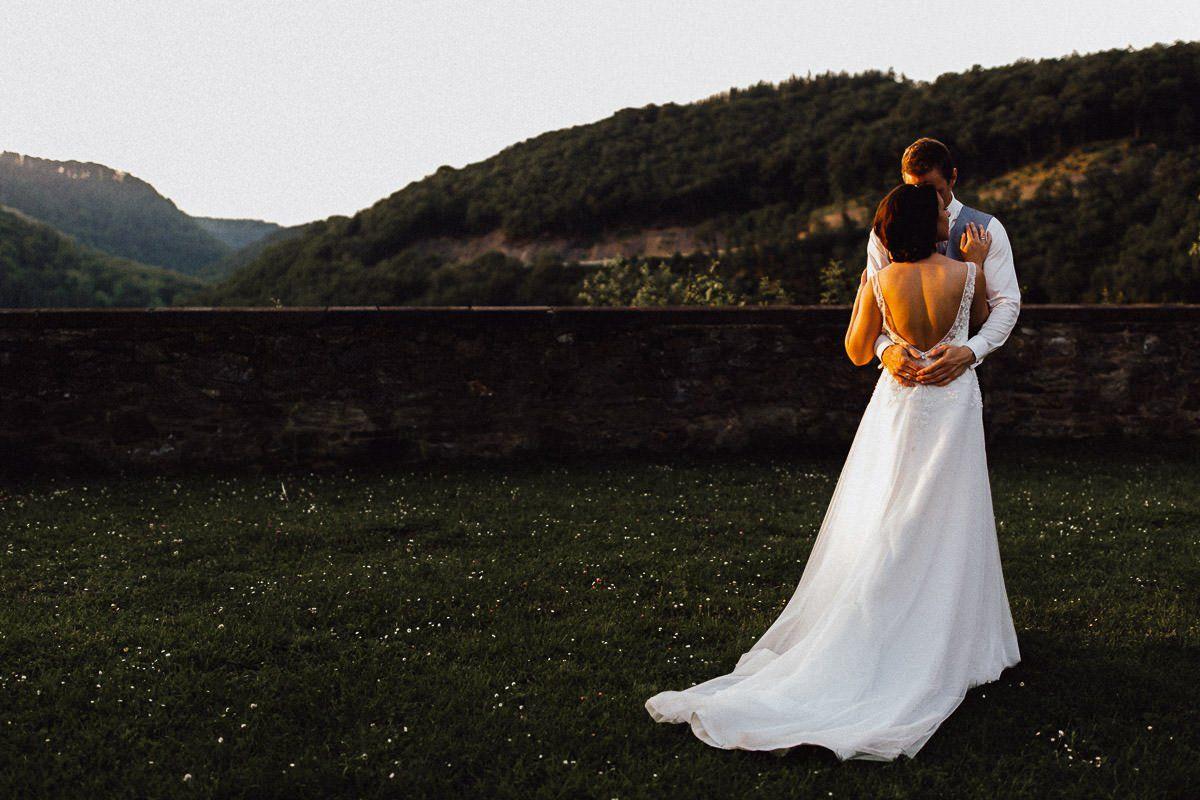 Hochzeitspaar küsst sich im Sonnenuntergang vor bergiger Kulisse