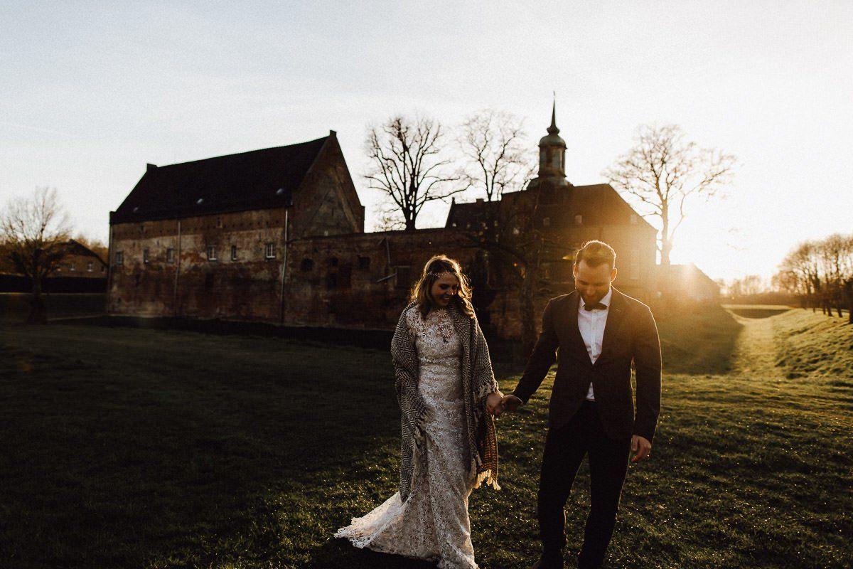 Hochzeitspaar im Sonnenuntergang vor einer Burg