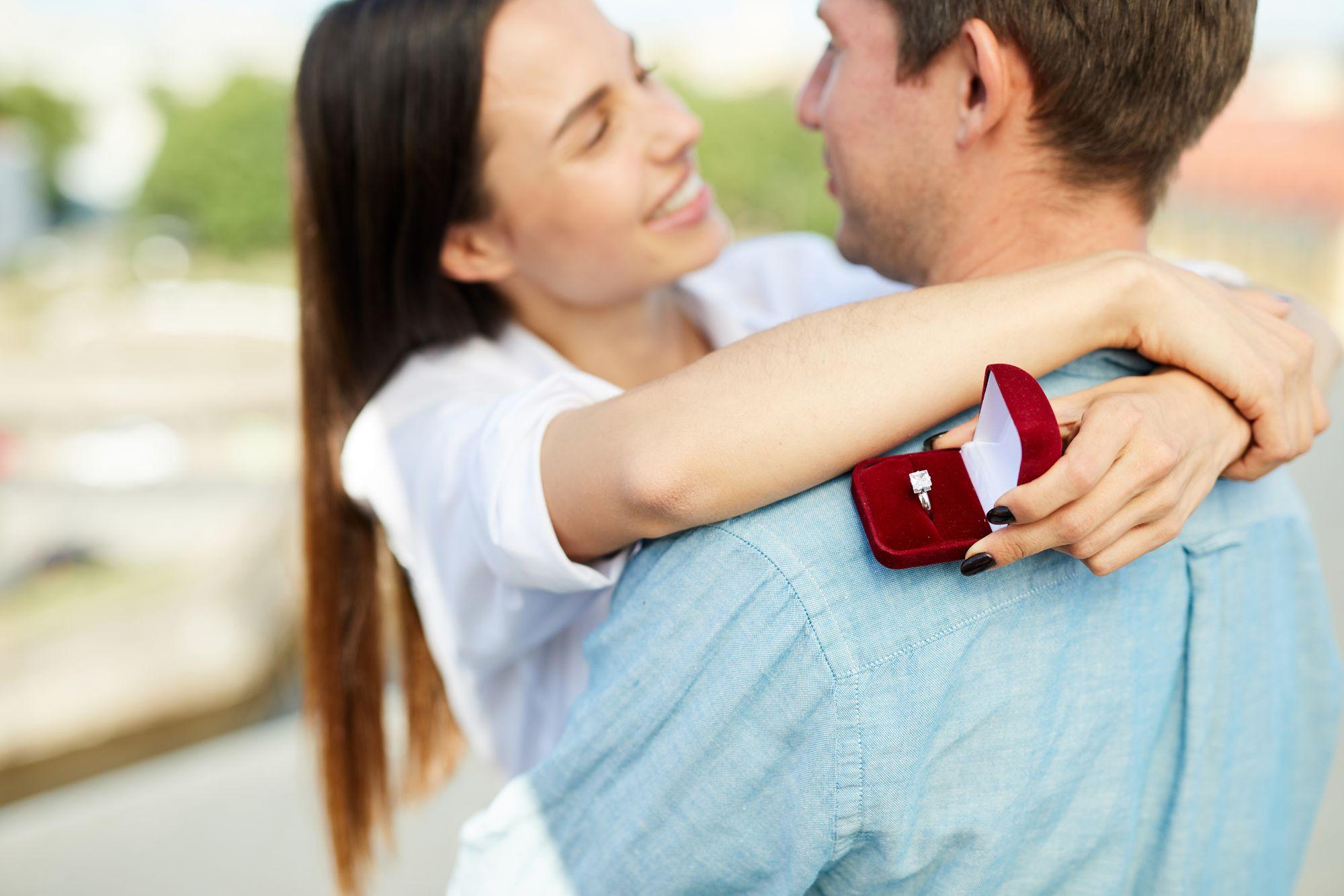Mann und Frau umarmen sich nach Heiratsantrag