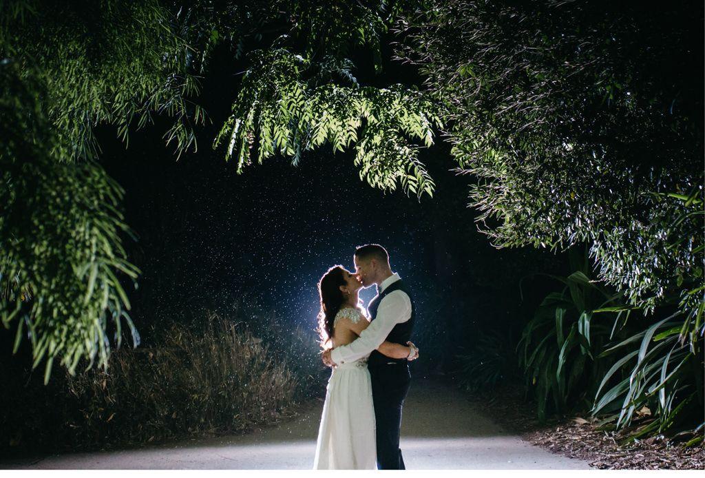 Hochzeit im Regen Brautpaar küsst sich im Regen