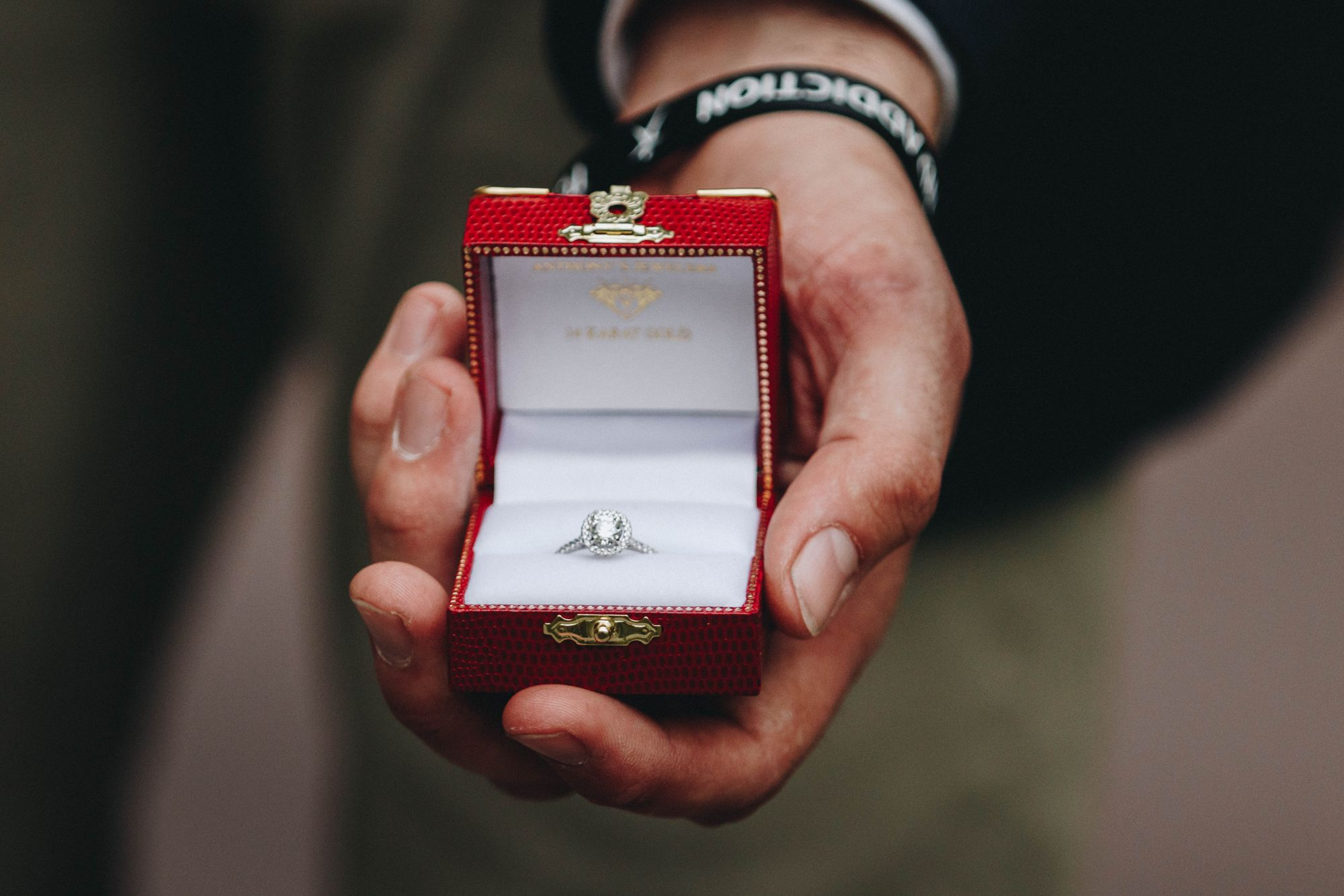 Mann hält einen Verlobungsring in einer roten Ringschatulle