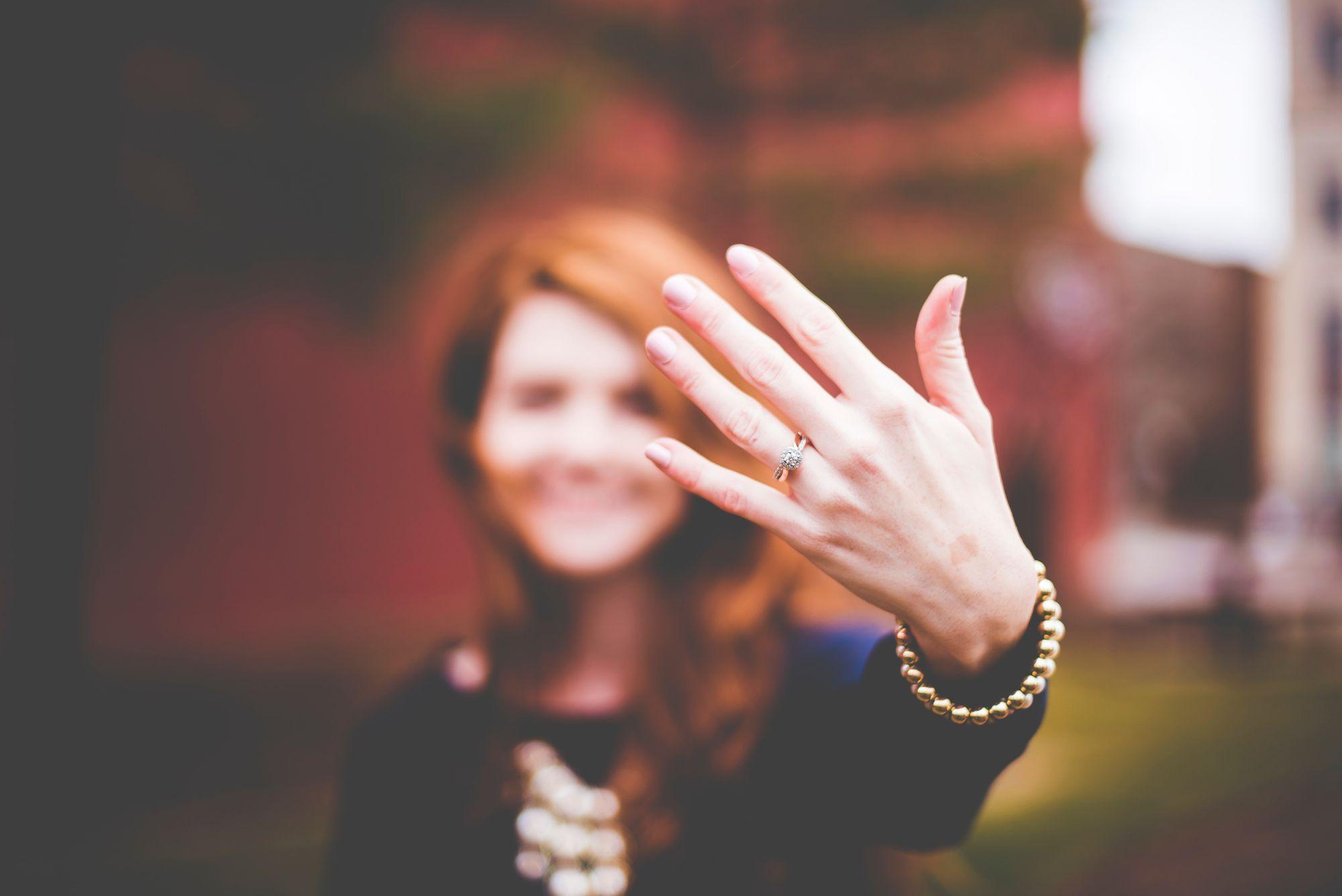 Frau trägt einen Verlobungsring am Ringfinger
