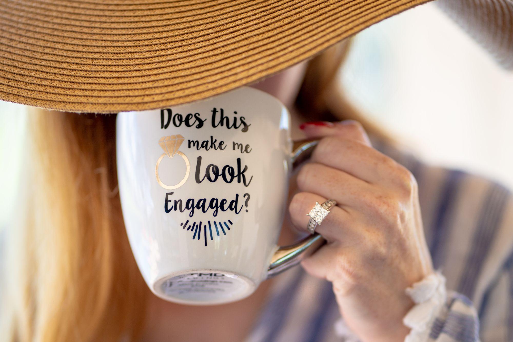 Frau trinkt aus einer Tasse, die auf ihre Verlobung hinweist