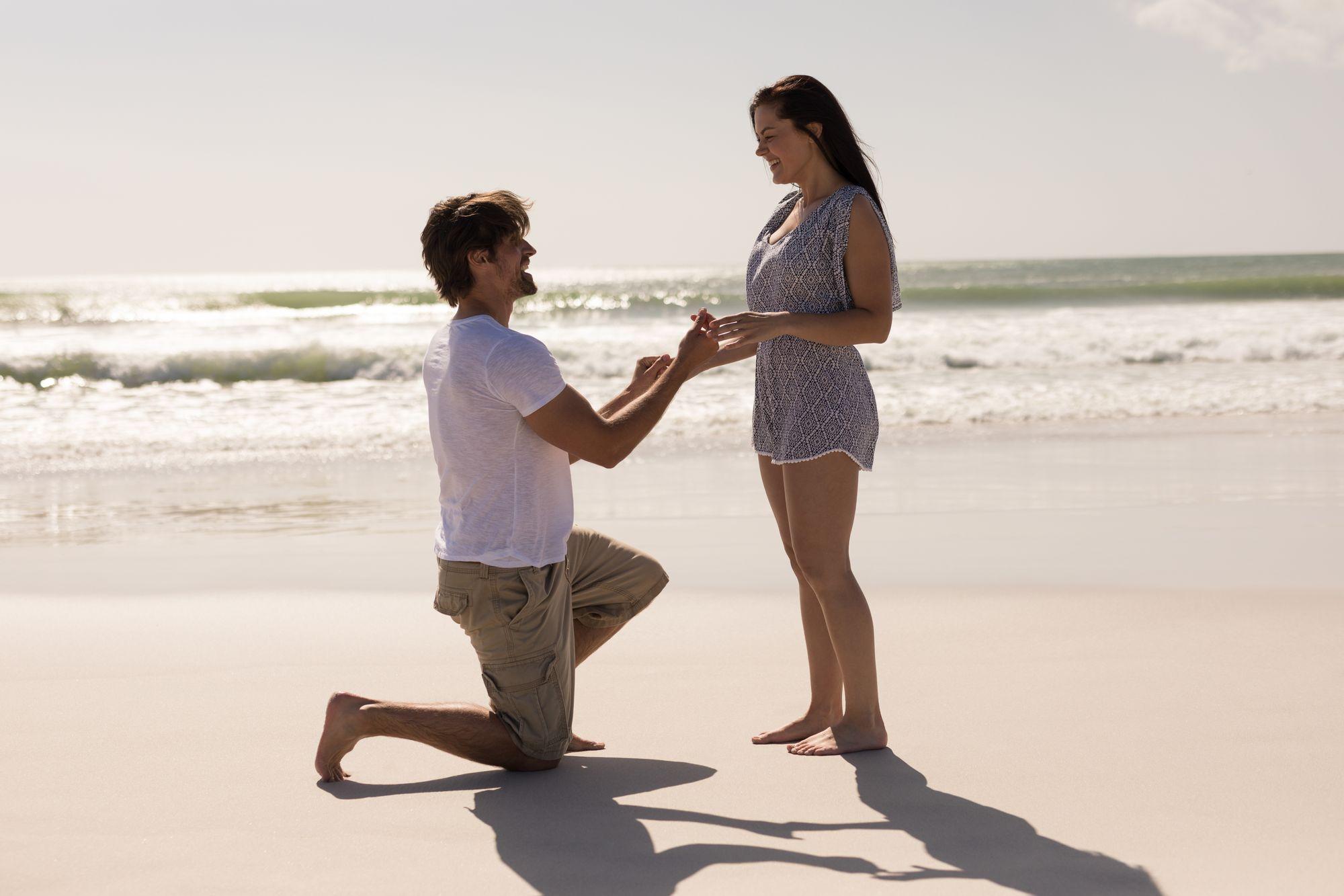 Mann macht Frau am Strand einen Antrag zur Verlobung