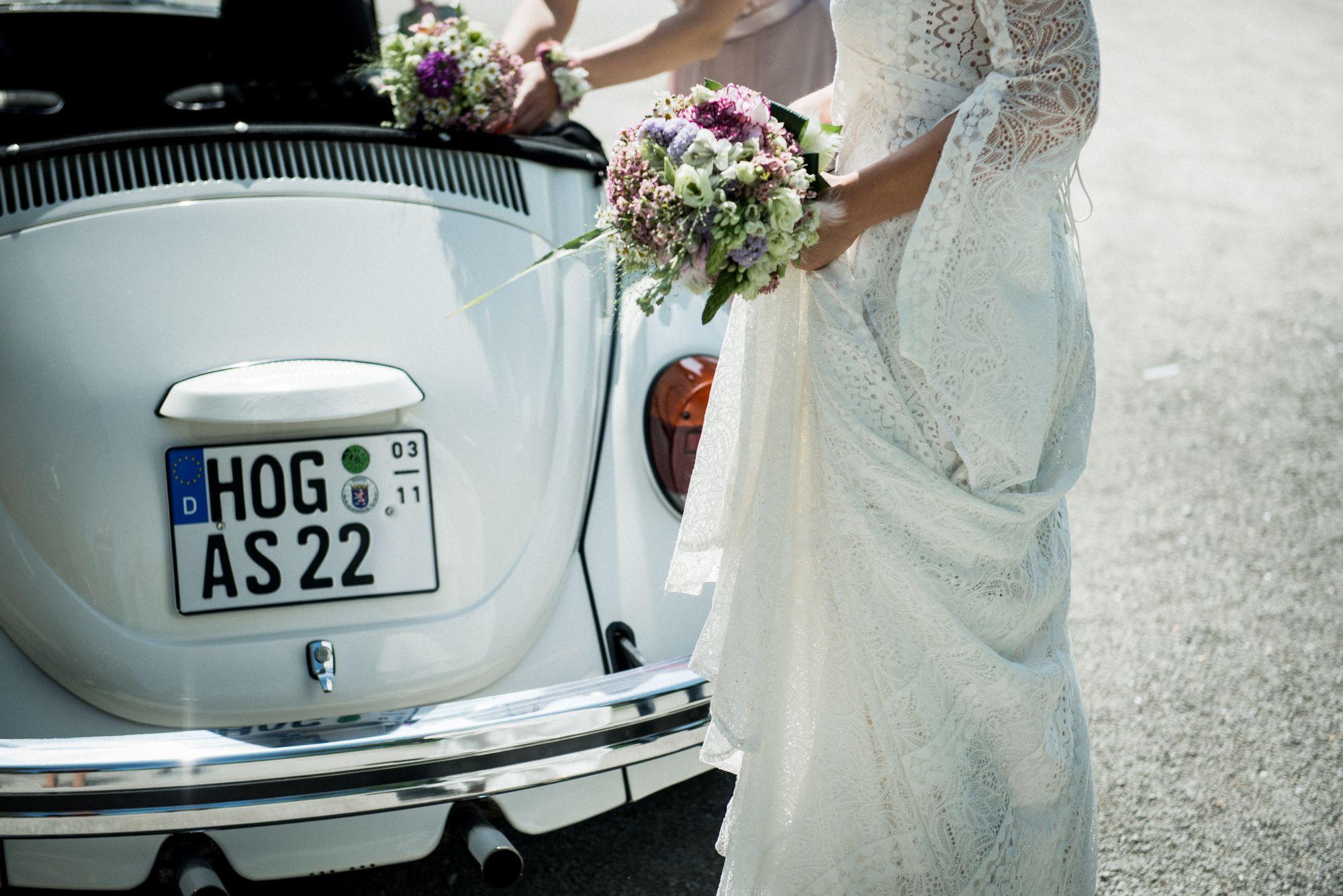 Braut-steht-in-Kleid-vor-Käfer