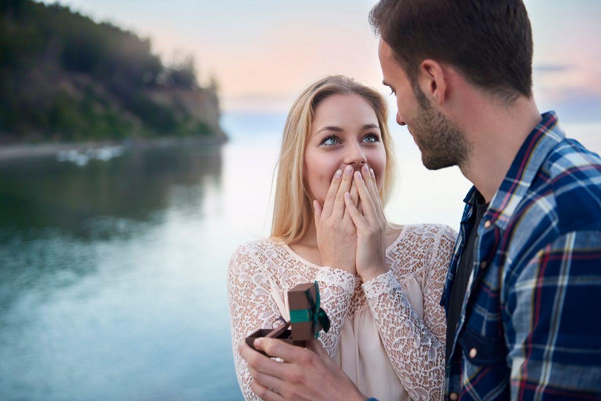 Mann macht Frau einen Heiratsantrag am Wasser