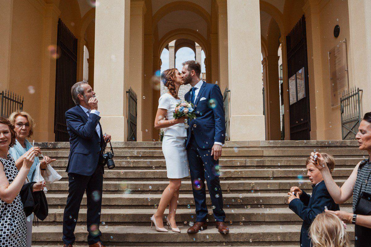 Hochzeitspaar küsst sich nach der Trauung vor dem Standesamt