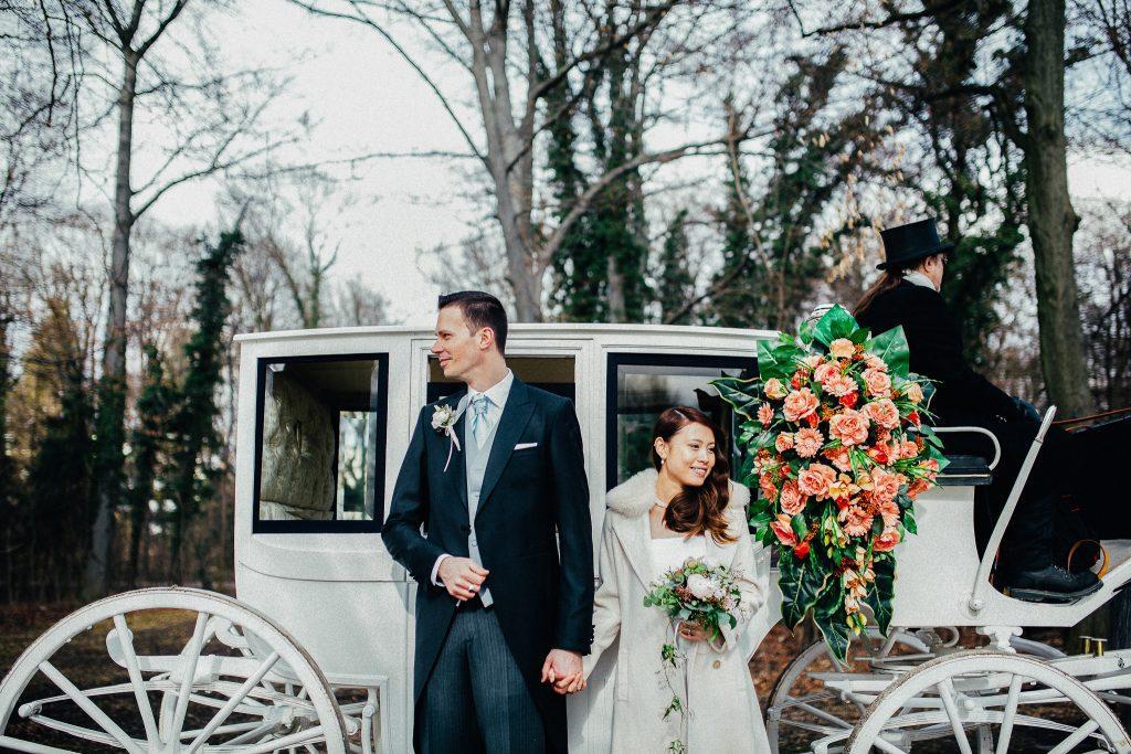 Brautpaar steht vor einer weißen Kutsche