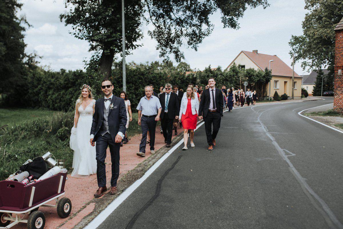 Hochzeitsgesellschaft läuft als Korso zur Location